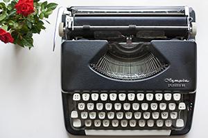 Vintage typewriter next to vase of roses