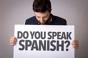 "Man holding sign asking ""Do you speak spanish?"""