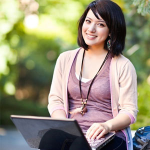 College student sitting on the ground with her computer in her lap.